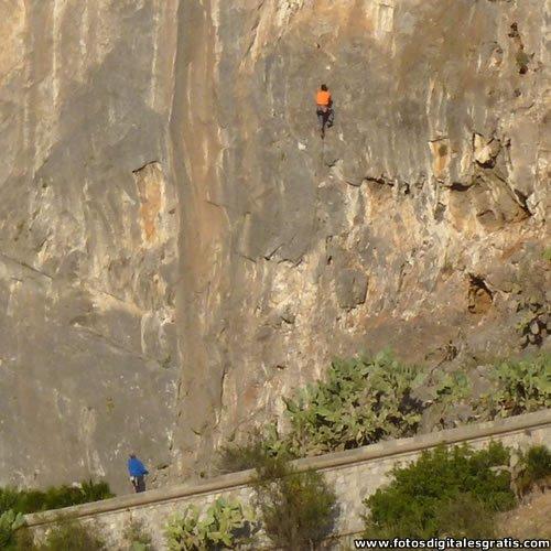 Paredes de piedra en la Garganta de los Vados y personas escalando